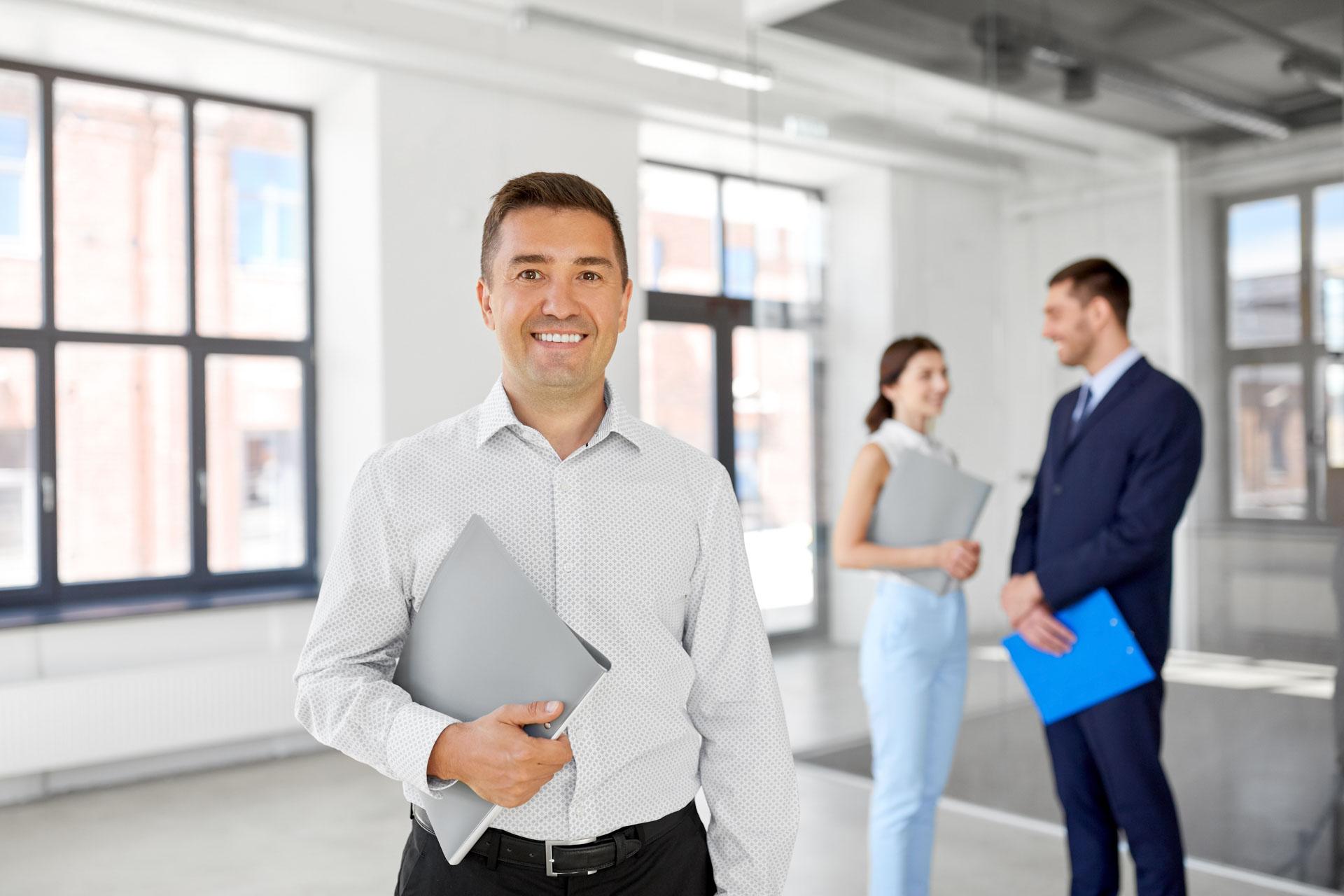 Immobiliengeschäft, Verkauf und Menschen Konzept - glücklich lächelnd Immobilienmakler oder Geschäftsmann mit Ordner und Kunden an neuen Büroraum