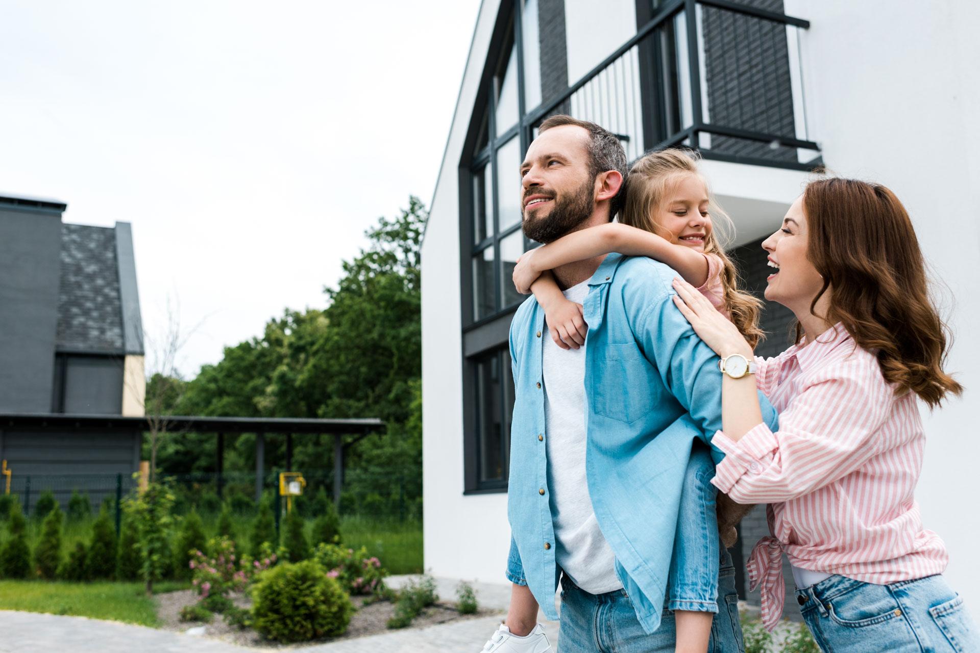 glücklicher Mann Huckepack Tochter in der Nähe fröhliche Frau und Haus