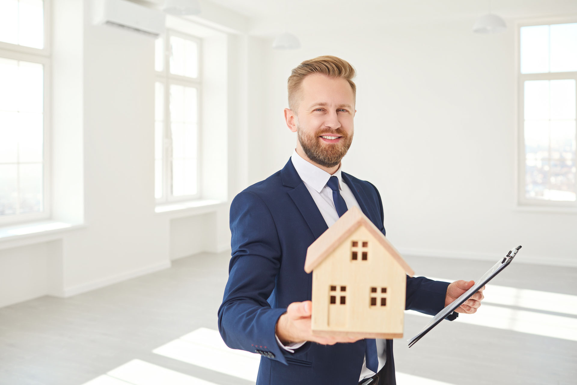 Immobilienmakler hält ein Modell des Hauses lächelnd in weißen Immobilien Zimmer Wohnung nach Hause.