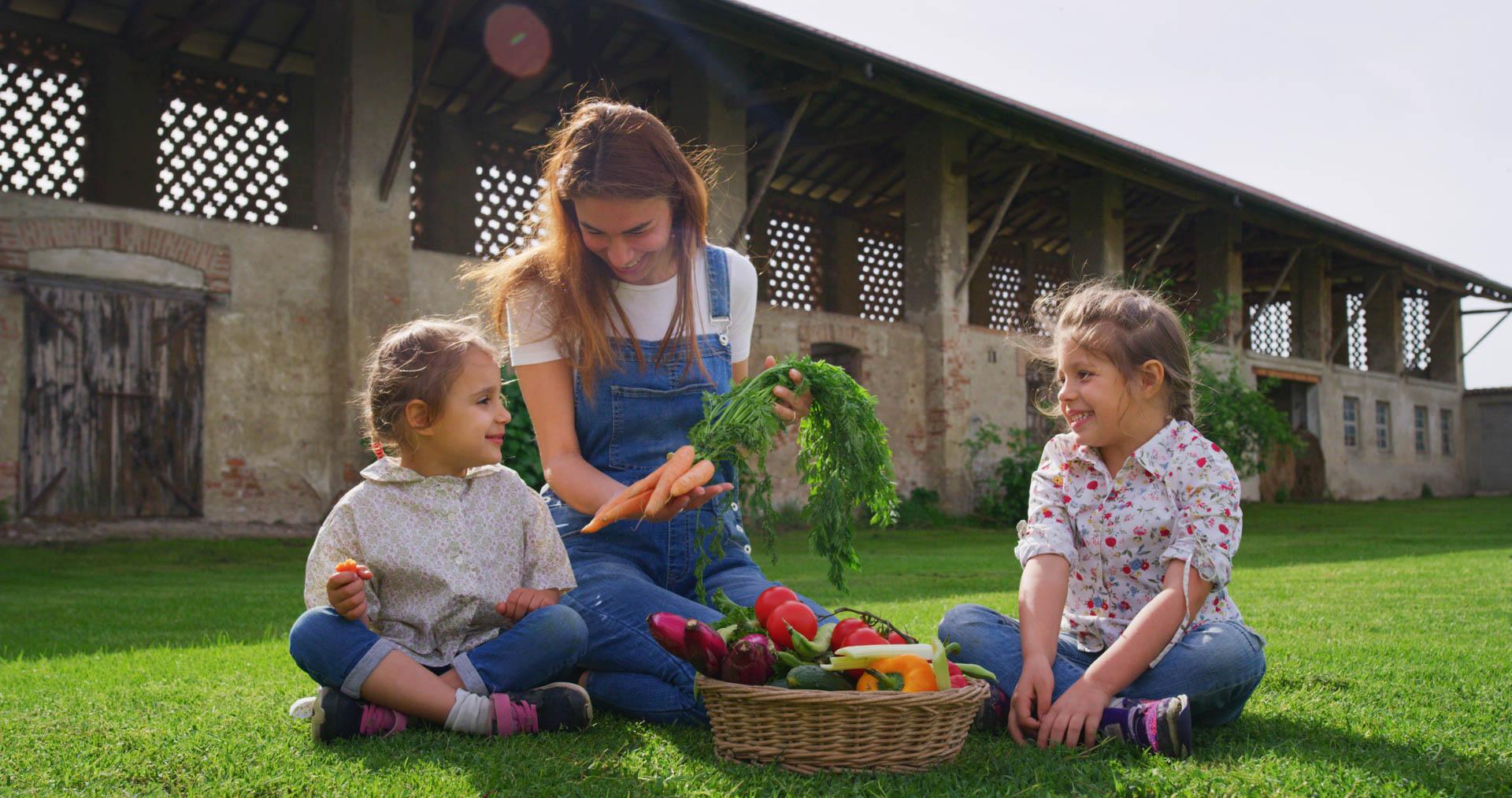Porträt einer glücklichen jungen Mutter Bauer zeigt frisches biologisches Gemüse