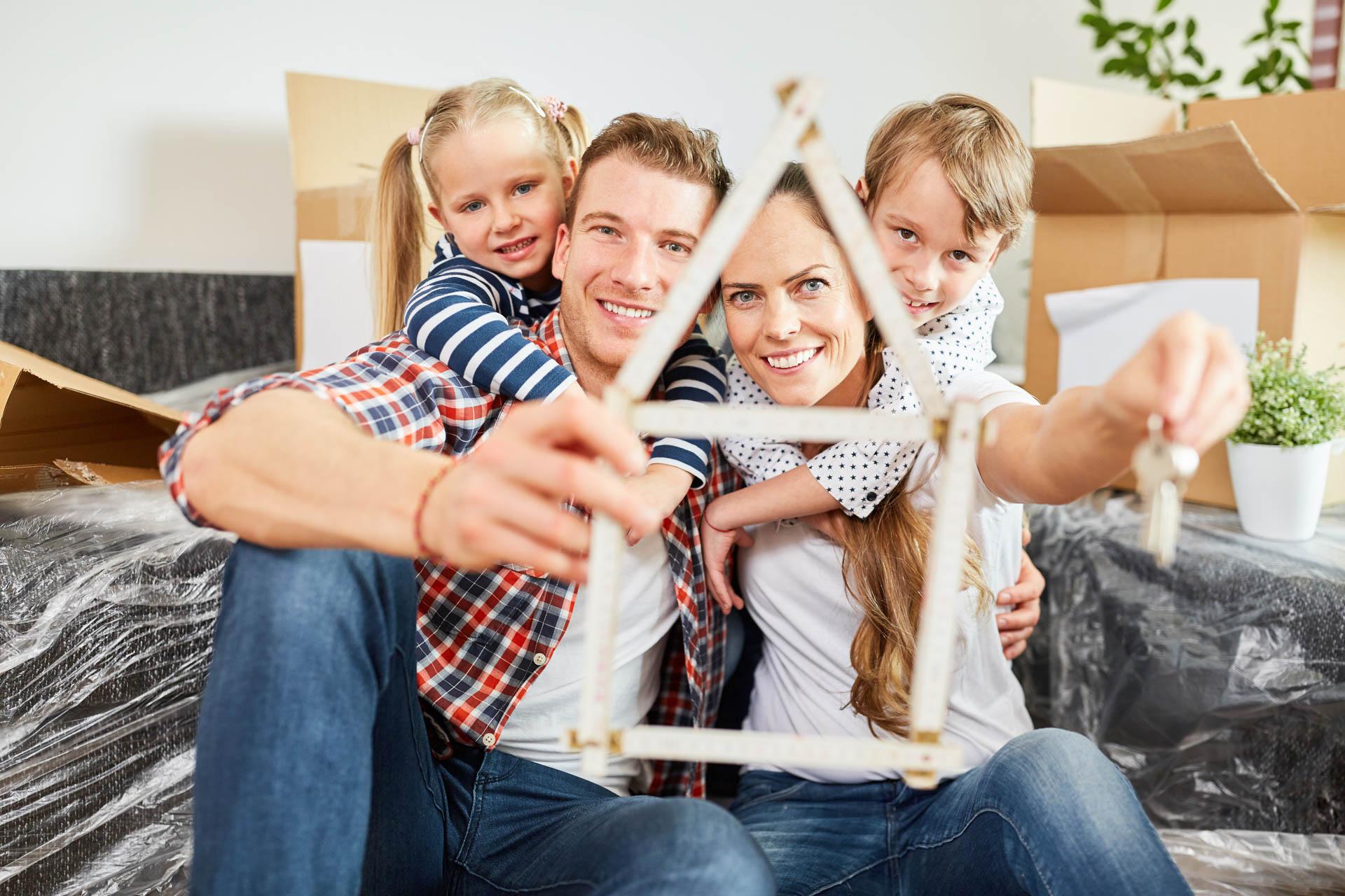 Familie und Kinder mit Zollstock in Form von Haus als Symbol für ihr Traumhaus